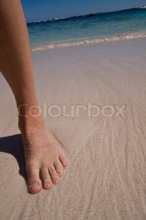 Cropped image of a foot on a beach