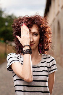 Red haired women with one eye closed by her hand