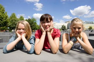 Three teenage girls with hands on their faces
