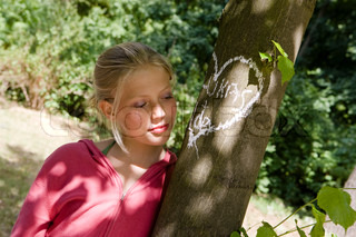 An in-love teenage girl standing next to a tree with a drawing of a heart