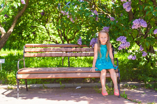 Adorable happy little girl in a lilac flower garden sitting on bench