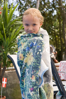 A young girl with wet hair wrapped with a beach towel