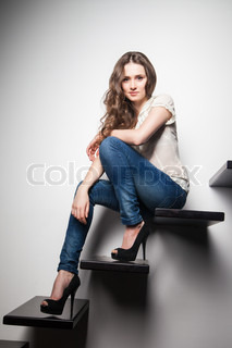 sexy woman sitting on stairs over grey