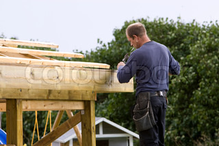 A male carpenter building a carport