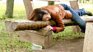 Drunk woman sleeping it off on a wooden bench