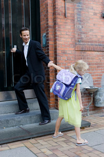 A young girl clings to her father on her first day in school