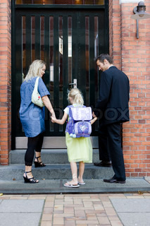 A young girl and her parents on her first day of school