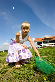 A young caucasian girl catching butterfly in the field