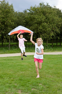 A caucasian girl and her brother flying a kite in the garden