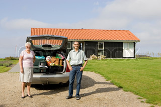 An elderly couple standing in front of their car and summer house