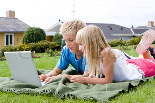 Caucasian children playing with their laptop in the garden