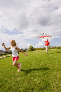 A father and daughter flying a kite in the garden