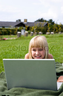 A smiling girl in the garden with her laptop