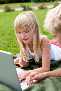 A brother and sister playing with their laptop computer in the garden