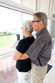 A loving elderly couple looking through a glass eindow