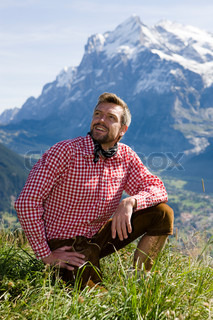 A man in bavarian costume enjoys the good weather