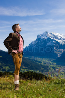 A man in Bavarian costume standing on top of a hill