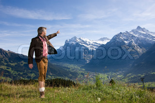 A man in Bavarian costumes pointing to the mountain in Switzerland