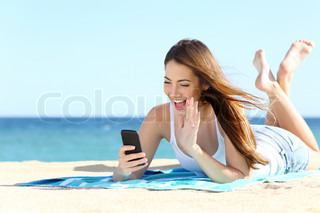 Teenager girl waving during a smart phone video call in vacations
