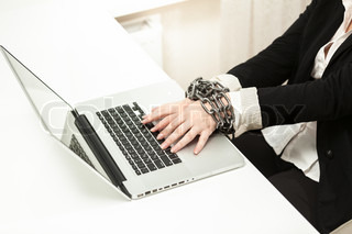 chained businesswoman typing on keyboard