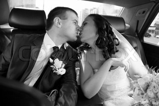 Portrait of bride and groom kissing on backseat of car