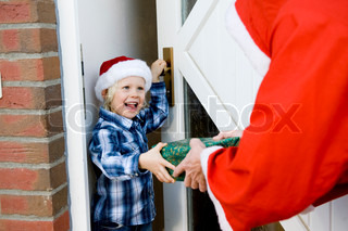 A happy caucasian boy receiving Christmas present from Santa Claus
