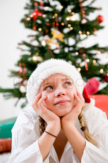 Girl daydreaming under the Christmas tree