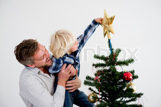 A father and his son putting the star on top of the Christmas tree