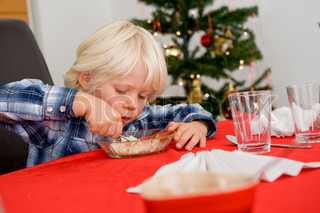 A caucasian boy eating his Christmas rice porridge