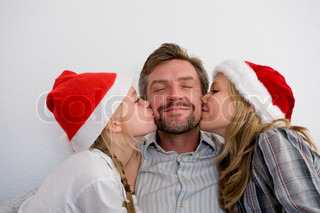 Two daughters kissing their father on Christmas day