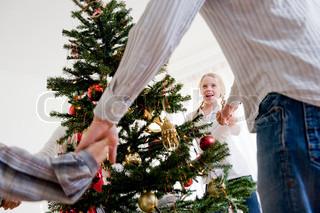 En familie der danser om juletræet hånd i hånd