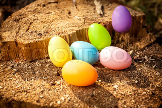 Shot of colorful easter eggs on wooden stump