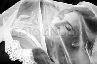 Portrait of groom kissing bride under white veil