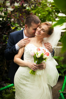 Groom kissing bride in neck at jungle