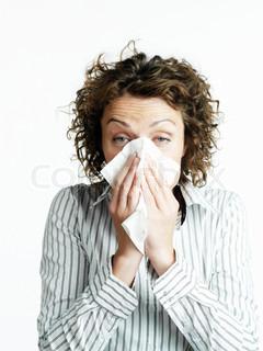 A sick businesswoman blows her nose