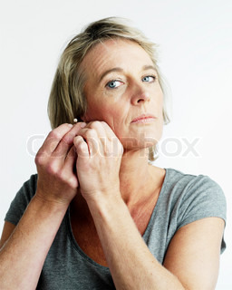 A matured woman putting on her earrings
