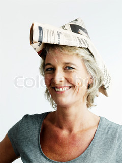 A smiling woman with a paper boat used as hat