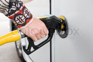 A man pumping gasoline in his car