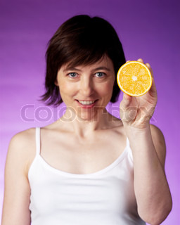 A woman holding a slice of orange