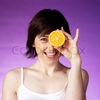A smiling woman holding a slice of orange