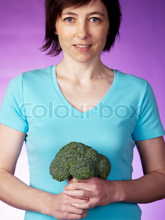 A woman holding a broccoli