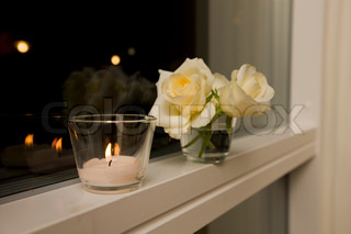 Candlelight and vase with roses on a window sill