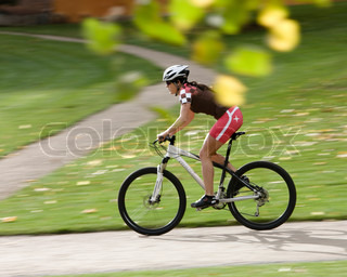 A young female athlete rides a bike in the park