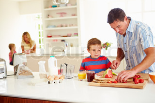 Son Helping Father To Prepare Family Breakfast In Kitchen