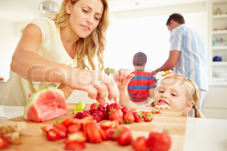 Daughter Helping Mother To Prepare Family Breakfast