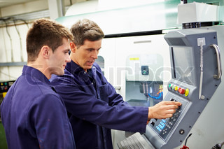 Engineer And Apprentice Using Automated Milling Machine