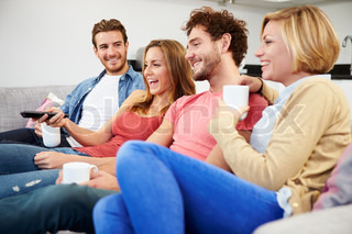 Group Of Friends Watching Television Together At Home