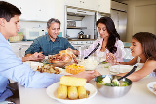 Family Sitting Around Table Saying Prayer Before Eating Meal