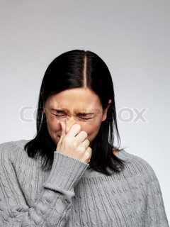A woman holds her nose to stop from sneezing