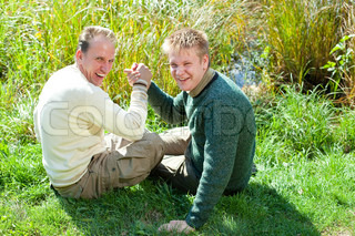 The father with the son are engaged in an armwrestling on the bank of a pond